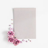 istock Flowers composition. Paper blank, purple flowers on white background. Flat lay, top view, copy space 1136850976