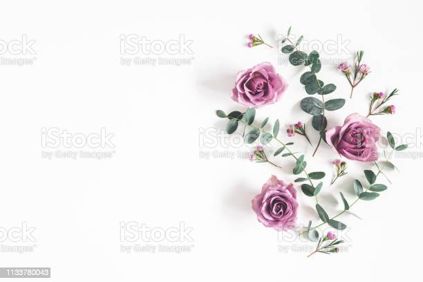 Photo of Flowers composition. Pattern made of eucalyptus branches and rose flowers on white background. Flat lay, top view, copy space