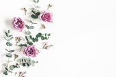 istock Flowers composition. Pattern made of eucalyptus branches and rose flowers on white background. Flat lay, top view, copy space 1134930443