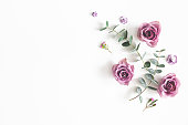 istock Flowers composition. Pattern made of eucalyptus branches and rose flowers on white background. Flat lay, top view, copy space 1136850980