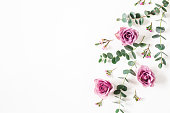 istock Flowers composition. Pattern made of eucalyptus branches and rose flowers on white background. Flat lay, top view, copy space 1248549298