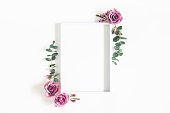 istock Flowers composition. Photo frame, eucalyptus branches and rose flowers on white background. Flat lay, top view, copy space 1136116511