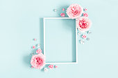 istock Flowers composition. Photo frame, rose flowers on pastel blue background. Valentines day, mothers day, womens day, spring concept. Flat lay, top view, copy space 1127776469