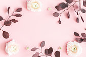 istock Flowers composition. Pink flowers and eucalyptus leaves on pastel pink background. Flat lay, top view, copy space 1141378885