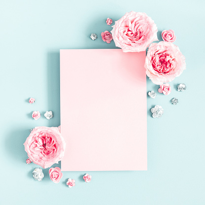Flowers composition. Pink paper blank, rose flowers on pastel blue background. Valentines day, mothers day, womens day, spring concept. Flat lay, top view, copy space, square