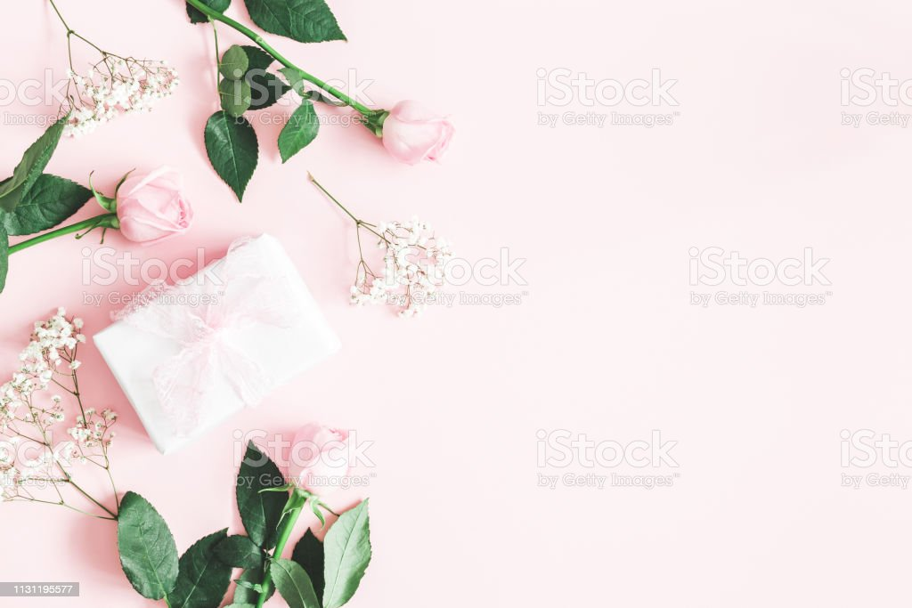 Flowers composition. Pink rose flowers, gift box on pastel pink...