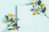 Flowers composition. Purple and yellow flowers, paper blank on pastel blue background. Spring concept. Flat lay, top view, copy space