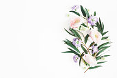 istock Flowers composition. Purple flowers and eucalyptus leaves on white background. Flat lay, top view, copy space 1141379031