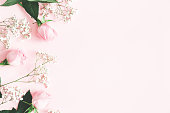 istock Flowers composition. Rose and gypsophila flowers on pastel pink background. Valentines day, mothers day, womens day concept. Flat lay, top view, copy space 1127559263