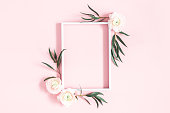 istock Flowers composition. White flowers, eucalyptus leaves, photo frame on pastel pink background. Flat lay, top view, copy space 1142359146