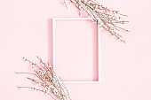 istock Flowers composition. White flowers, photo frame on pastel pink background. Flat lay, top view, copy space 1142359087