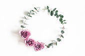 istock Flowers composition. Wreath made of eucalyptus branches and rose flowers on white background. Flat lay, top view, copy space 1134930124