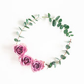 istock Flowers composition. Wreath made of eucalyptus branches and rose flowers on white background. Flat lay, top view 1251514417