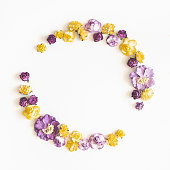 istock Flowers composition. Wreath made of purple and yellow flowers on white background. Flat lay, top view, copy space, square 1136116549