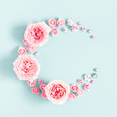 istock Flowers composition. Wreath made of rose flowers on pastel blue background. Mothers day, womens day, spring concept. Flat lay, top view, copy space, square 1130299172