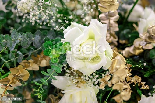 Flowers decorate wedding green, white and gold.