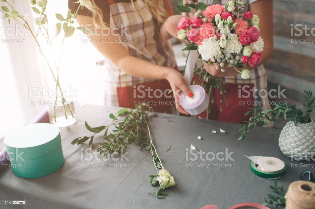 Flowers delivery top view. Florists creating order, making rose...