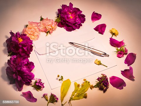 968272356istockphoto Flowers, envelope and pen on a red 538663700