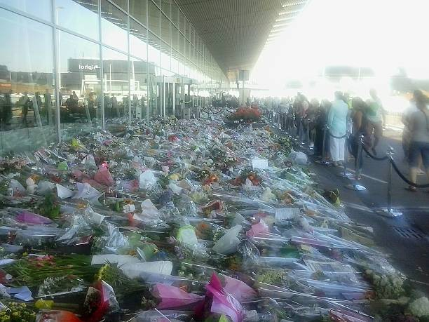 Flowers for some killed in plane crash 2 Schiphol, The Netherlands - July 23rd, 2014: Many Memorial flower bouquets for the dead (not only Dutch) of the MH17 flight, recently apparently shot down by a Ukrainian missile. The flowers are just outside Amsterdam Airport, presented by citizens and Authorities. On the right, many people greatly sad. apparently stock pictures, royalty-free photos & images