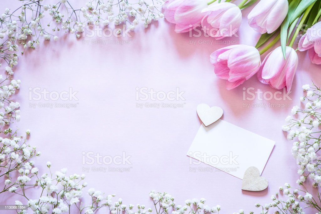 Blumenrahmen mit Grußkarte auf Holztisch – Foto