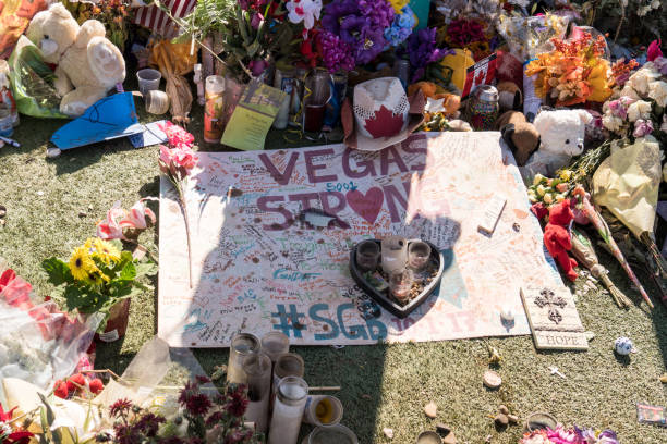 Flowers, gifts candles line memorial park at the Welcome to Las Vegas sign by the Mandalay Bay on the Vegas Strip to remember the victims killed in the Las Vegas attack OCT 13 2017 LAS VEGAS NV: Flowers, gifts candles line memorial park at the Welcome to Las Vegas sign by the Mandalay Bay on the Vegas Strip to remember the victims killed in the Las Vegas attack mass murder stock pictures, royalty-free photos & images