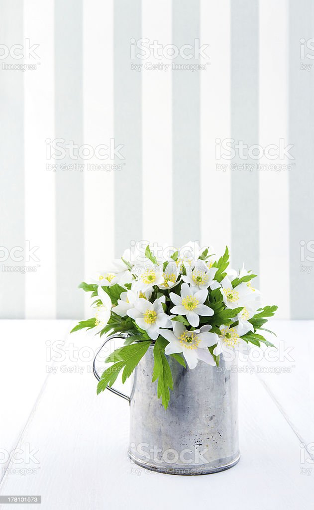 Flowers in a metal cup on vintage background stock photo