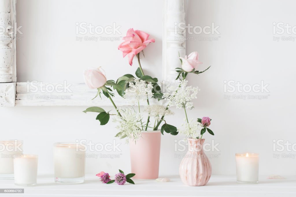 flowers in a vase and candles on white background stock photo