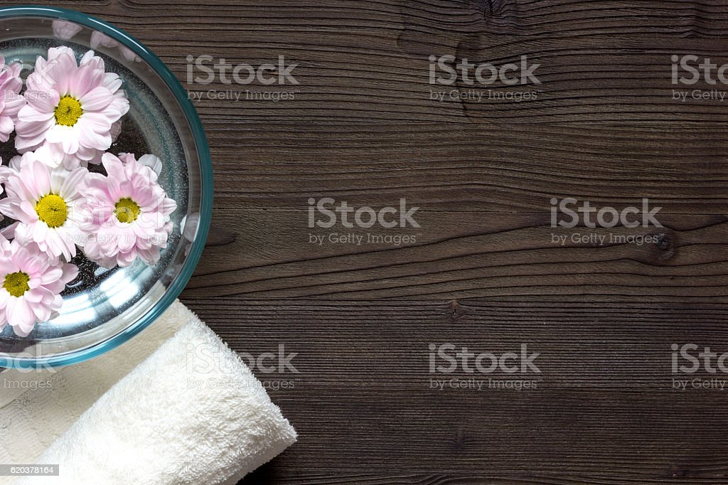 flowers in bowl and oil top view on wooden background zbiór zdjęć royalty-free