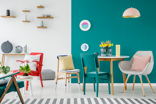 Chairs at wooden table against green wall in colorful apartment interior with flowers