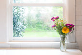 Bouquet of flowers by window, high key, in glass jar with copy space. Bright and airy in modern farmhouse kitchen