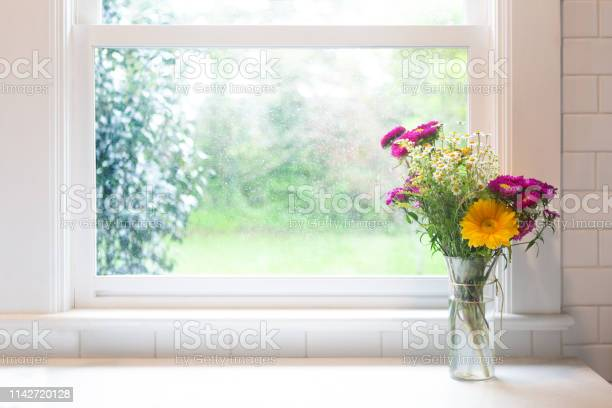 Photo of Flowers in front of window - high key with copyspace