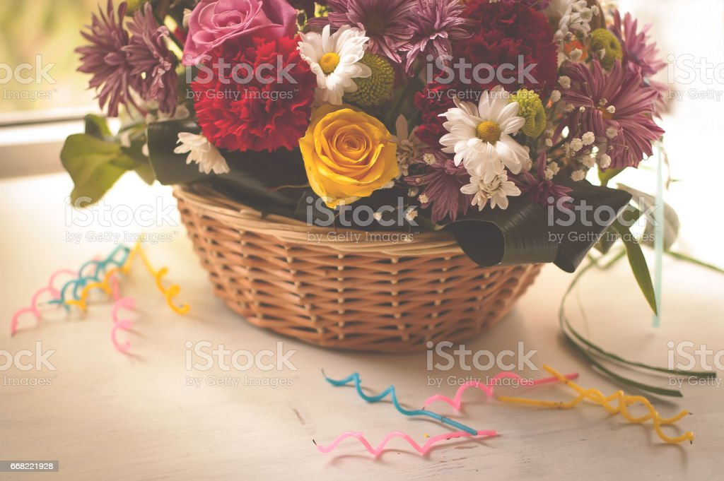 Flowers In The Basket And Happy Birthday Candles On Wooden Background