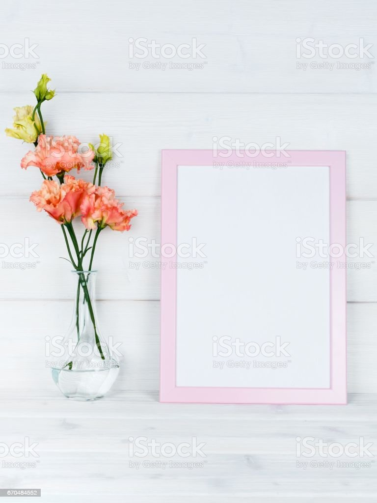 Flowers in vase and a photo frame on a wooden background. stock photo
