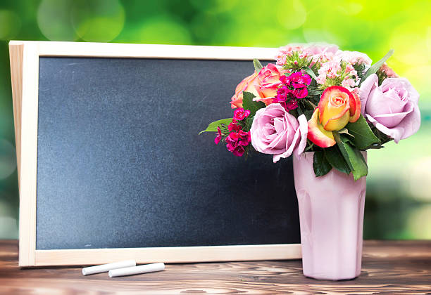 flowers in vase and chalckboard empty copy space background. - teachers day stock photos and pictures