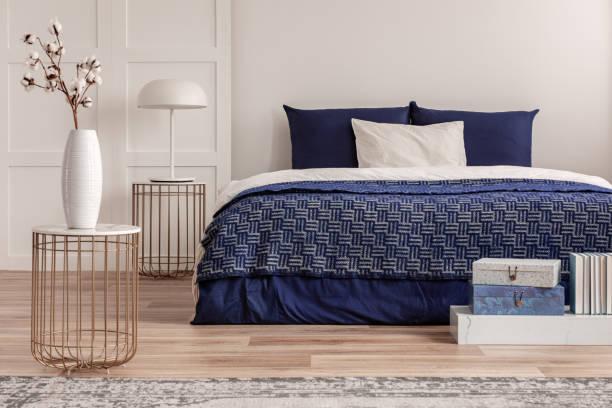 blumen in vase auf nachttisch neben kingsize-bett mit marineblauen bettwäsche - marineblau schlafzimmer stock-fotos und bilder