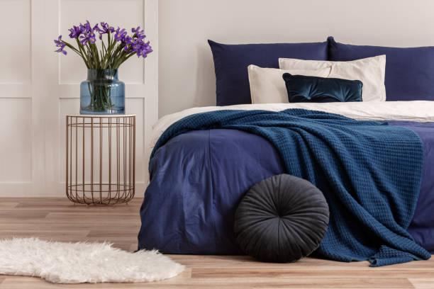 blumen in vase auf stilvolle nachttisch tisch neben bequemen bett mit weißen und blauen bettwäsche - marineblau schlafzimmer stock-fotos und bilder
