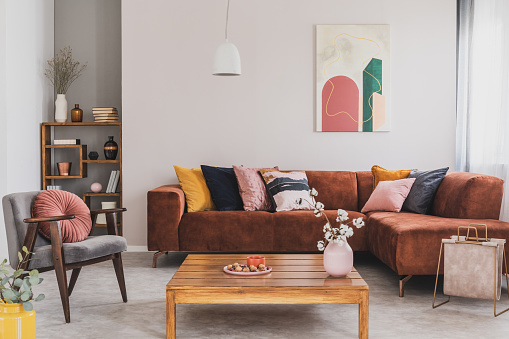 Flowers in vase on wooden coffee table in fashionable living room interior with brown corner sofa with pillows and abstract painting on the wall