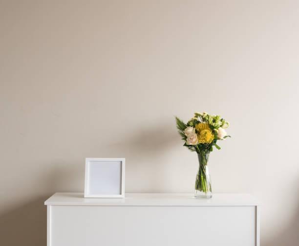 blumen in vase mit leeren quadratischen rahmen auf sideboard - anrichte weiß stock-fotos und bilder