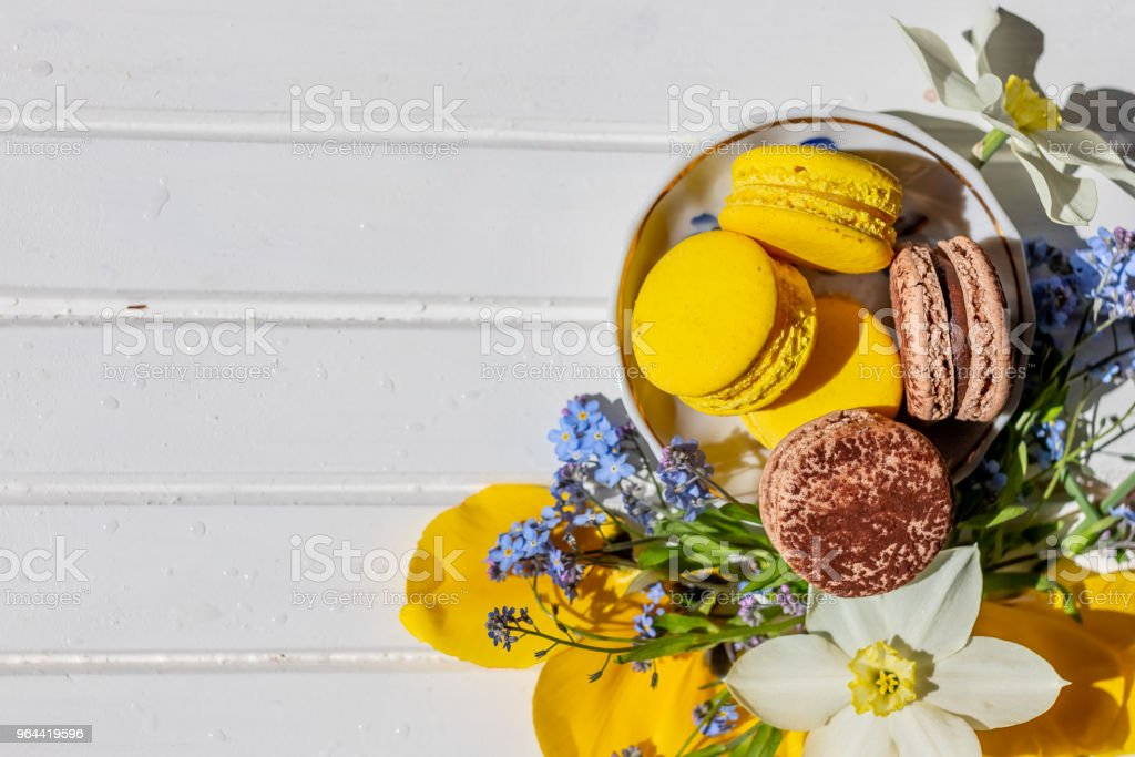 Flowers, macarons in pastel color on the white wooden background, top view. Copy space.chocolate macaroon and lemon dessert isolated. - Royalty-free Backgrounds Stock Photo