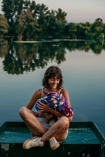 Beautiful young adult woman sitting crossed legged outdoors on the boat with colorful flowers holding on her chest and looking thankful.