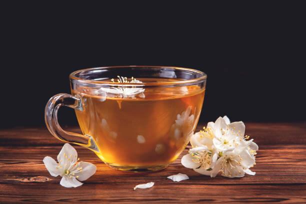 Blumen von Philadelphus irgendwo genannt Jasmin oder Mock Orange und Tasse mit duftenden Jasmin Tee auf dunklen Holztisch – Foto