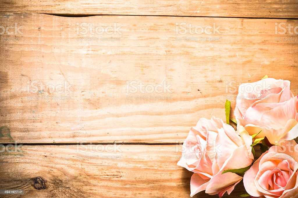 Flowers of roses arranged on brown, vintage wooden planks background. stock photo
