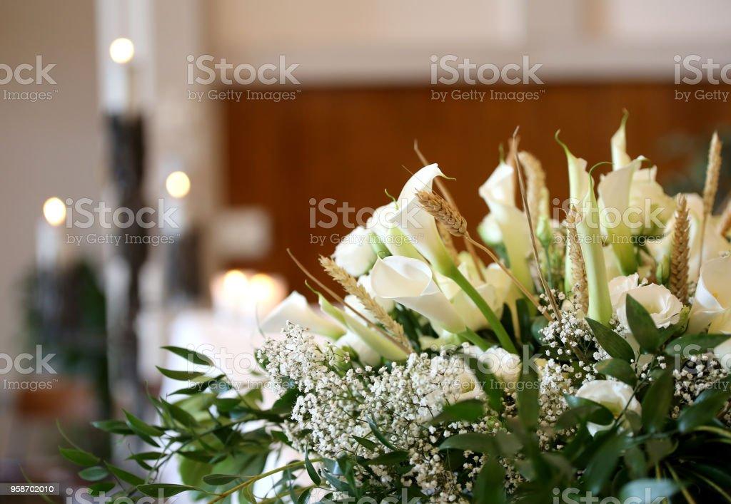 Blumen auf dem Altar in der Kirche und die Kerzen auf Hintergrund – Foto