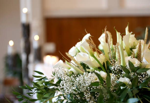 flowers on an altar in the church and the candles on background - funerale foto e immagini stock