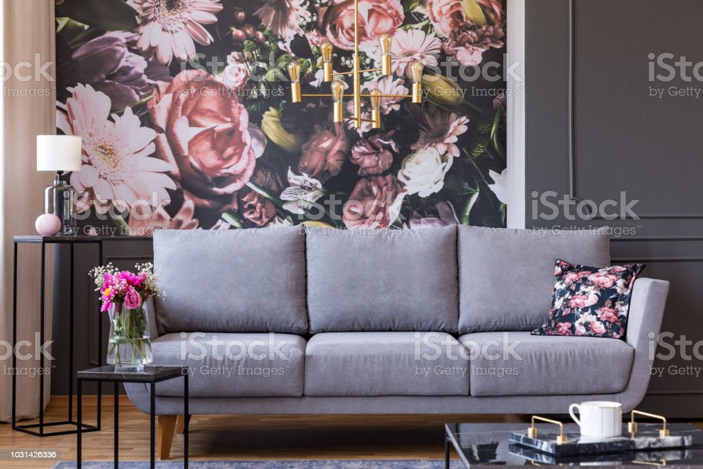 Flowers On Black Table And Grey Sofa In Living Room Interior With