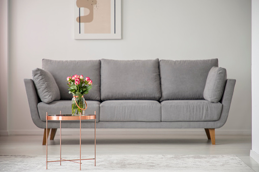 Flowers on copper table in front of grey sofa in bright living room interior with poster. Real photo