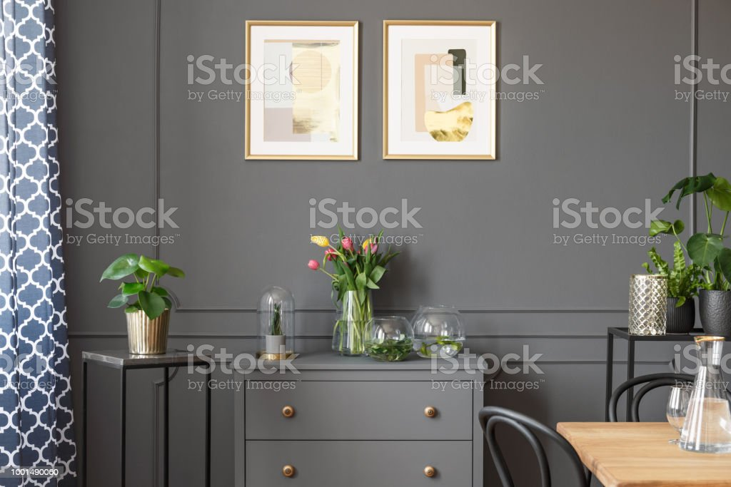 Flowers on grey cabinet under posters in minimal loft interior with plants. Real photo stock photo