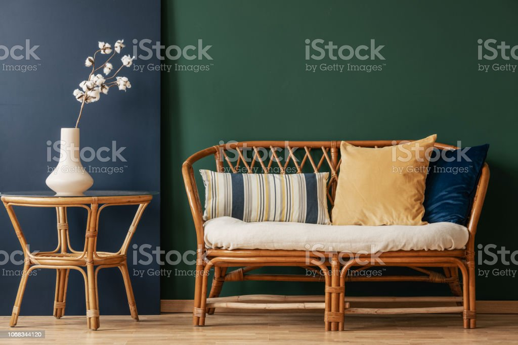 Flowers on natural table next to sofa with cushions in green and blue...