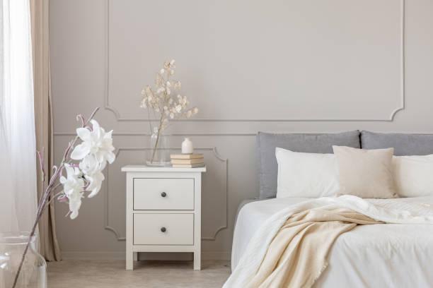 Blumen auf Nachttisch tisch in reizvollen Schlafzimmer Interieur mit grau und weiß Design – Foto