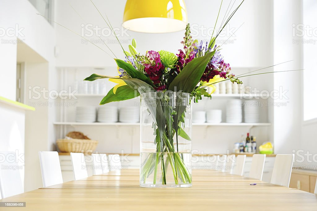 Flowers on table in bright large kitchen stock photo